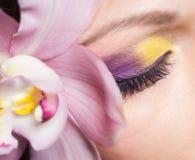 Ragazza con il fiore dell'orchidea Fotografia Stock
