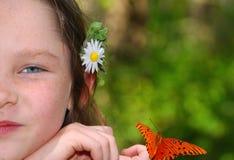 Ragazza con il fiore e la farfalla Immagine Stock