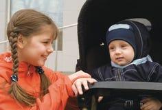 Ragazza con il fratello in un carrello (1) Fotografia Stock