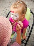 Ragazza con il fronte verniciato Fotografia Stock