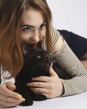Ragazza con il gatto maligno nero su bianco quasi isolato fotografia stock