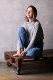 Ragazza con il ginocchio piegato che si siede su una piattaforma Fondo grigio Immagine Stock Libera da Diritti