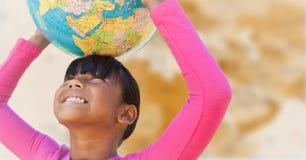 Ragazza con il globo sulla testa contro la mappa marrone confusa Immagine Stock