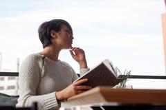 Ragazza con il libro in caffè esterno Fotografia Stock Libera da Diritti