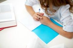 Ragazza con il libro che scrive al taccuino alla scuola Fotografia Stock Libera da Diritti