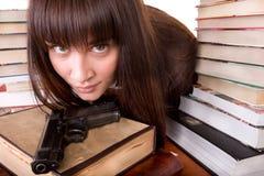 Ragazza con il libro e l'arma del mucchio. Fotografia Stock