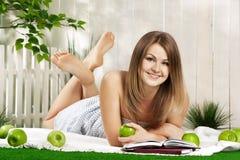 Ragazza con il libro e mela nel giardino Fotografia Stock