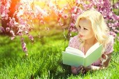 Ragazza con il libro Giovane donna bionda che si trova sull'erba Fotografie Stock