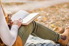 Ragazza con il libro sulle gambe che legge alla retro coperta immagini stock