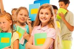 Ragazza con il manuale nel grande gruppo di bambini Fotografia Stock Libera da Diritti