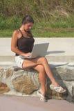 Ragazza con il marciapiede della spiaggia del computer portatile Immagini Stock