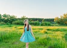 Ragazza con il mazzo di camomille in un campo con erba alta Fotografia Stock