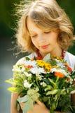 Ragazza con il mazzo di wildflowers all'aperto Immagini Stock