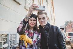 Ragazza con il modello che prende un selfie fuori della costruzione della sfilata di moda di Dirk Bikkembergs per la settimana 20 Immagine Stock