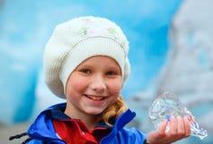 Ragazza con il pezzo del ghiaccio vicino al ghiacciaio di Nigardsbreen (Norvegia) Fotografia Stock Libera da Diritti
