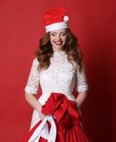 Ragazza con il sorriso affascinante, in cappello di Santa, con la grande borsa con Fotografia Stock Libera da Diritti