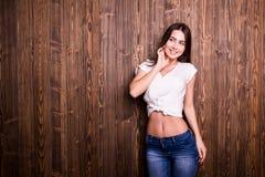 Ragazza con il sorriso piacevole contro la parete di legno Fotografia Stock Libera da Diritti