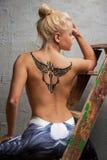 Ragazza con il tatuaggio temporaneo nero dipinto con le pitture per body art fotografia stock