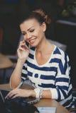 Ragazza con il telefono cellulare in caffè Immagine Stock