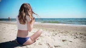 Ragazza con il telefono cellulare che si siede sulla sabbia vicino al mare ed al cielo blu Primo amore stock footage