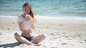 Ragazza con il telefono cellulare che si siede sulla sabbia vicino al mare ed al cielo blu Primo amore video d archivio