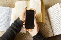 Ragazza con il telefono cellulare ed i libri Immagine Stock