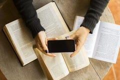 Ragazza con il telefono cellulare ed i libri in bianco Fotografie Stock Libere da Diritti