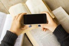 Ragazza con il telefono cellulare ed i libri in bianco Fotografia Stock