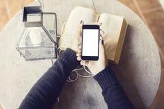 Ragazza con il telefono cellulare ed i libri in bianco Immagine Stock