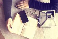 Ragazza con il telefono cellulare ed il libro Fotografie Stock