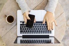Ragazza con il telefono cellulare, il computer portatile e la tazza di caffè Fotografia Stock