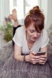 Ragazza con il telefono che si trova sul suo stomaco sullo strato Immagini Stock