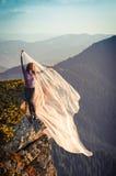 Ragazza con il tessuto rosa-chiaro che gioca con il vento sulle montagne Fotografie Stock