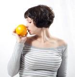 Ragazza con l'arancio Fotografie Stock