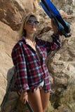 Ragazza con l'arpone in camicia della flanella sulla spiaggia rocciosa immagine stock