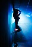Ragazza con l'ente piacevole che posa ad un night-club ad una siluetta del partito Fotografie Stock