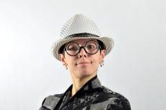Ragazza con l'espressione ridicola, il cappello ed i vetri Fotografia Stock