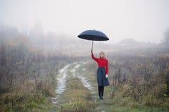 Ragazza con l'ombrello nel campo di autunno fotografia stock libera da diritti