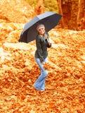 Ragazza con l'ombrello nella sosta di autunno Immagini Stock