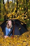 Ragazza con l'ombrello sotto i fogli di caduta Fotografie Stock Libere da Diritti