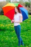 Ragazza con l'ombrello in un prato verde Immagini Stock