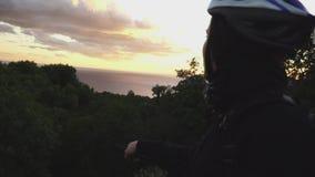 Ragazza con la bici che sta sulla strada e che ammira il paesaggio del mare al tramonto stock footage