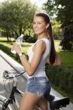 Ragazza con la bicicletta e la bottiglia di acqua Fotografie Stock Libere da Diritti