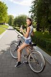 Ragazza con la bicicletta e la bottiglia di acqua Immagini Stock Libere da Diritti