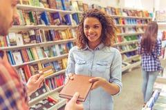 Ragazza con la carta di credito alla libreria Immagine Stock