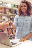 Ragazza con la carta di credito alla libreria Fotografia Stock Libera da Diritti