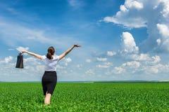 Ragazza con la cartella che cammina sull'erba Fotografia Stock