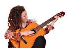 Ragazza con la chitarra acustica del gioco dei dreadlocks immagine stock