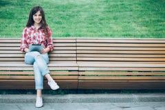 Ragazza con la compressa che si siede su un banco di parco Immagini Stock