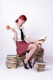 Ragazza con la lecca-lecca che si siede su un mucchio dei libri Immagini Stock